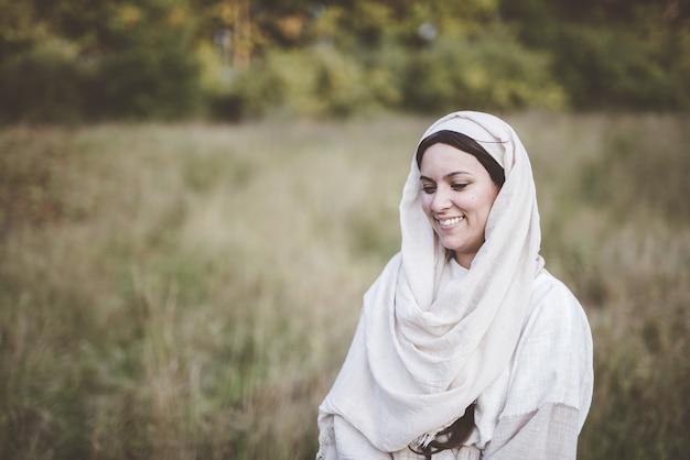 Tiro de foco superficial de una mujer vistiendo una túnica bíblica y sonriendo
