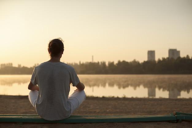 Tiro de hombre joven sano tomando un descanso después del entrenamiento de la mañana.