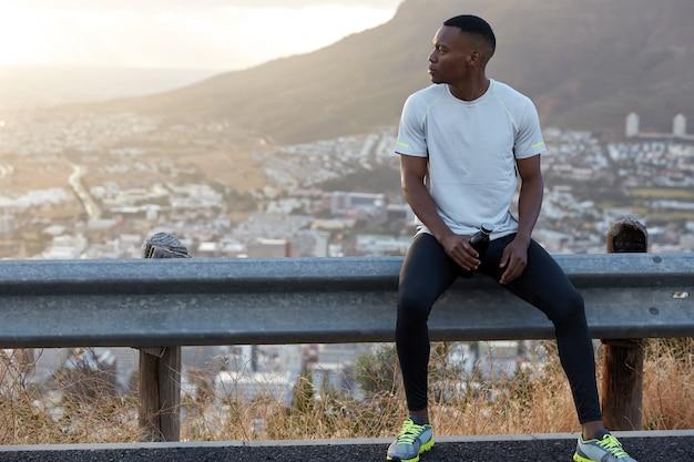 Tiro horizontal al aire libre de un hombre de piel oscura con camiseta casual, zapatillas de deporte, lleva una botella de agua, concentrado a un lado, tiene un descanso después del entrenamiento matutino solo, se siente deshidratado, tiene ejercicios matutinos