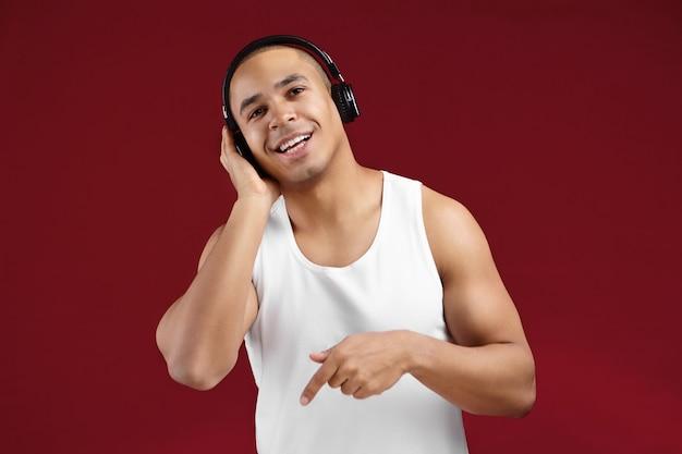Tiro horizontal de amistoso joven guapo afroamericano en elegante camisa sin mangas sonriendo felizmente y señalando con el dedo mientras escucha música en auriculares, cantando una melodía