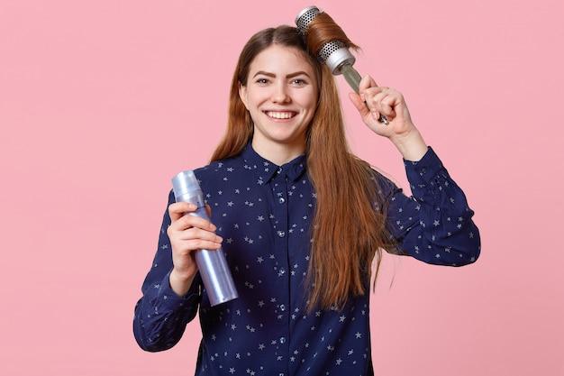 Tiro horizontal de apuesto sonriente mujer europea con cabello largo, utiliza cepillo para el cabello y laca para el cabello, vestido con elegante camisa