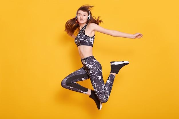 Tiro horizontal de la atractiva chica fitness excitado, joven bailarina en ropa deportiva saltando de alegría aislado sobre pared amarilla deportiva femenina vestidos top negro y leggins. concepto de cuidado saludable.
