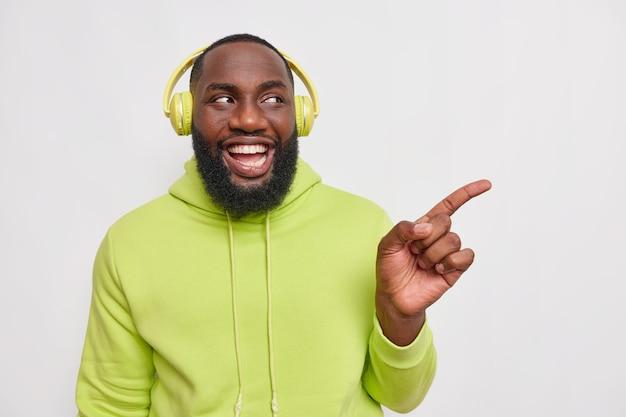 Tiro horizontal de feliz alegre chico hipster con barba espesa escucha música en auriculares lleva puntos casuales con capucha en el espacio en blanco da paso o dirección aislada en blanco