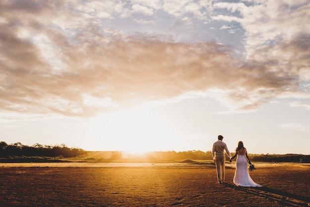 Tiro horizontal de un hombre y una mujer en traje de novia cogidos de la mano durante el atardecer