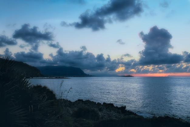 Tiro horizontal del mar en calma bajo el cielo nublado loco en la noche