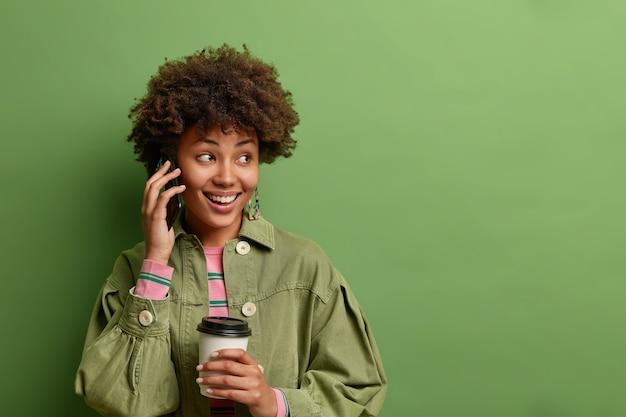 Tiro horizontal de mujer bonita afroamericana tiene conversación telefónica mantiene el teléfono inteligente cerca de la oreja, bebidas, café para llevar, mira hacia otro lado con una sonrisa suave aislada sobre el espacio de copia de la pared verde