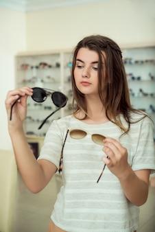 Tiro horizontal de mujer joven femenina de compras, sosteniendo dos pares de elegantes gafas de sol