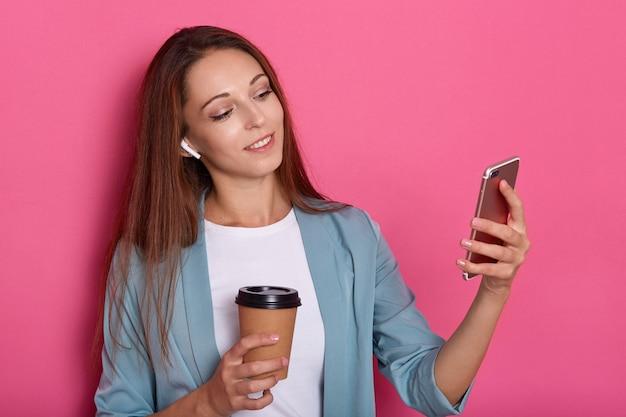 Tiro horizontal de mujer sonriente con cabello largo hermoso haciendo selfie