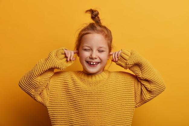 Tiro horizontal de niño pequeño alegre optimista tapona los oídos con los dedos índices, se ríe positivamente, tiene moño de jengibre, viste suéter de punto de gran tamaño, aislado en la pared amarilla. detén este sonido