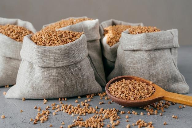 Tiro horizontal de trigo sarraceno asado en sacos y cuchara. granos sin gluten. cereales crudos cosechados. concepto de comida vegana natural