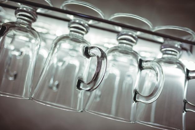 Tiro inclinable de tazas de pinta en el estante en el bar