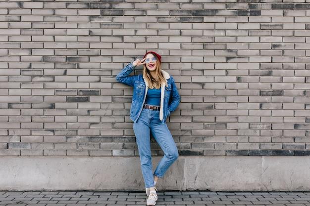 Tiro integral de dama emocional en jeans de pie con el signo de la paz en la pared de ladrillo. mujer muy bien formada en traje de mezclilla posando en la calle junto a la pared.