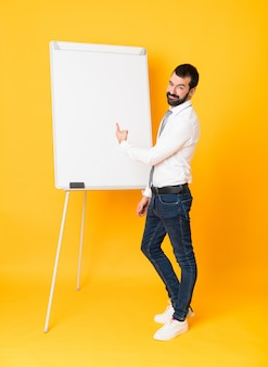 Tiro integral del empresario dando una presentación en la pizarra sobre amarillo aislado apuntando hacia atrás