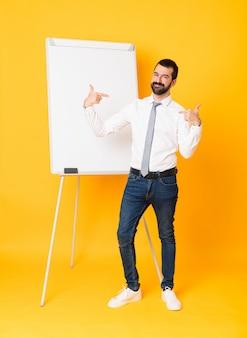 Tiro integral del empresario dando una presentación en pizarra sobre amarillo aislado orgulloso y satisfecho
