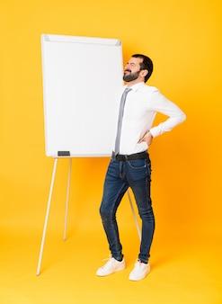 Tiro integral del empresario dando una presentación en la pizarra sobre amarillo aislado que sufre de dolor de espalda por haber hecho un esfuerzo