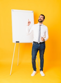 Tiro integral del empresario dando una presentación en la pizarra sobre fondo amarillo aislado apuntando hacia arriba y sorprendido