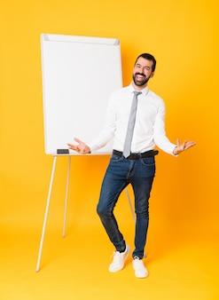 Tiro integral del empresario dando una presentación en el pizarrón sobre amarillo aislado sonriente