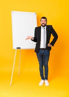 Tiro integral del empresario dando una presentación en el pizarrón sobre amarillo aislado