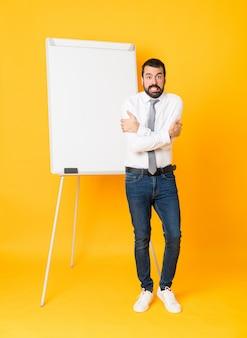 Tiro integral del empresario dando una presentación en el pizarrón sobre congelación amarilla aislada