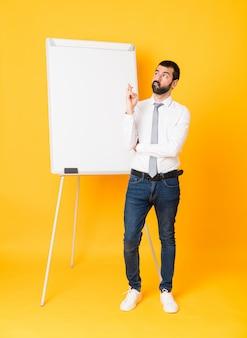 Tiro integral del empresario dando una presentación en el pizarrón