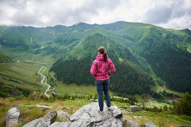 Tiro integral de una excursionista femenina de pie en la cima de una montaña mirando a su alrededor