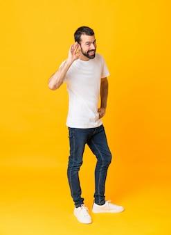 Tiro integral del hombre con barba sobre amarillo aislado escuchando algo poniendo la mano sobre la oreja