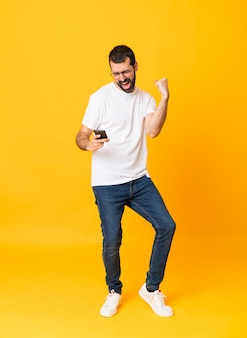 Tiro integral del hombre con barba sobre amarillo aislado con teléfono en posición de victoria