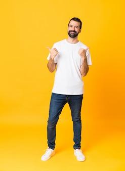 Tiro integral del hombre con barba sobre fondo amarillo aislado con pulgares arriba gesto y sonriendo