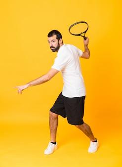 Tiro integral del hombre jugando tenis sobre amarillo aislado