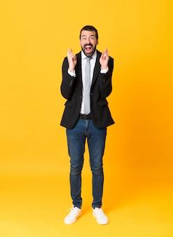 Tiro integral del hombre de negocios sobre amarillo aislado con cruzar los dedos