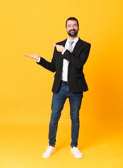 Tiro integral del hombre de negocios sobre amarillo aislado que sostiene el copyspace imaginario en la palma para insertar un anuncio