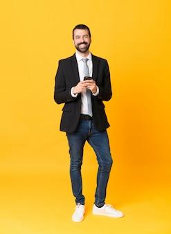 Tiro integral del hombre de negocios sobre fondo amarillo aislado enviando un mensaje con el móvil