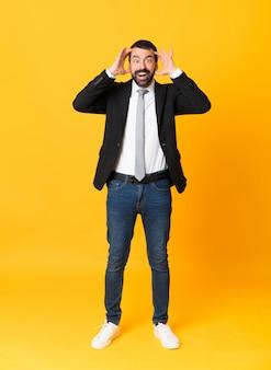 Tiro integral del hombre de negocios sobre fondo amarillo aislado con expresión de sorpresa