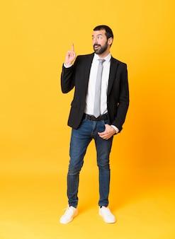 Tiro integral del hombre de negocios sobre fondo amarillo aislado pensando una idea apuntando el dedo hacia arriba