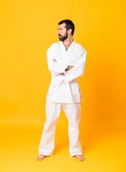 Tiro integral del hombre sobre amarillo aislado haciendo karate manteniendo los brazos cruzados