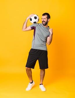 Tiro integral del hombre sobre fondo amarillo aislado con balón de fútbol celebrando una victoria