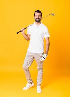 Tiro integral del hombre sobre la pared amarilla aislada jugando al golf