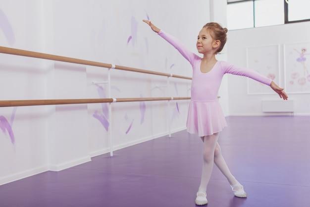 Tiro integral de una linda joven bailarina bailando en la escuela de ballet con gracia, copie el espacio