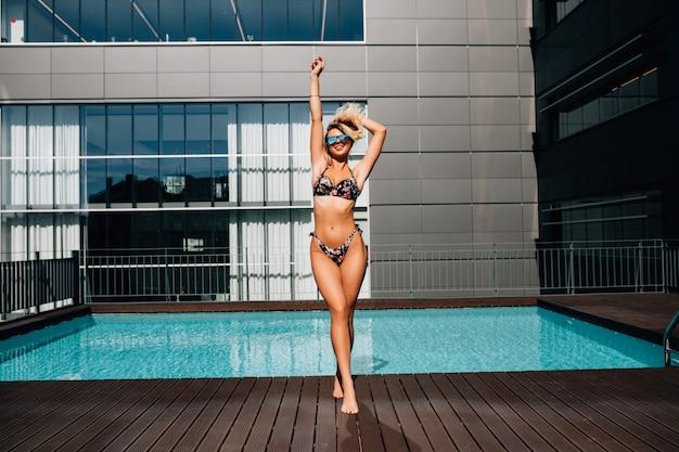 Tiro integral de una mujer joven delgada en traje de baño junto a la piscina.