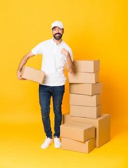 Tiro integral del repartidor entre cajas sobre amarillo aislado con expresión facial sorpresa