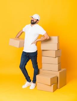 Tiro integral del repartidor entre cajas sobre amarillo aislado que sufre de dolor de espalda por haber hecho un esfuerzo