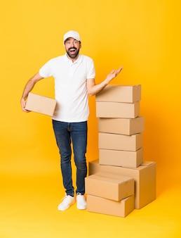 Tiro integral del repartidor entre cajas sobre fondo amarillo aislado con expresión facial sorprendida