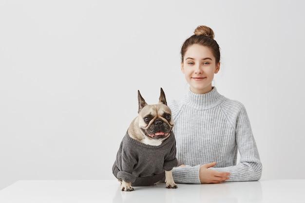 Tiro interior de alegre amante de las mascotas con cabello castaño en moño. ama de casa posando con su perro de pedigrí vestido con puente sentado en la mesa disfrutando juntos. expresiones humanas positivas