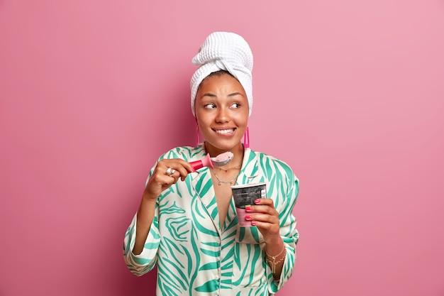 Tiro interior de una alegre joven de piel oscura que muerde los labios disfruta comiendo un apetitoso helado frío con una cuchara y pasa el tiempo libre en casa vestida con ropa casual aislada sobre una pared rosa