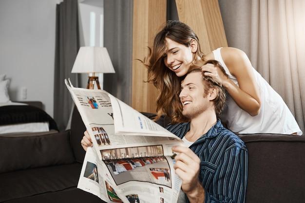 Tiro interior de la atractiva pareja caucásica enamorada, sentada en la sala de estar mientras lee el periódico y se ríe, disfrutando del ocio. después de una larga relación, los socios decidieron vivir juntos.