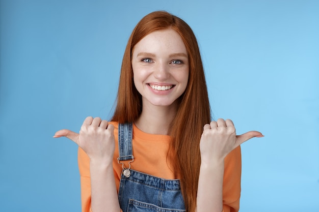 Tiro interior carismático asertivo feliz sonriente pelirroja mujer naranja camisa mono de mezclilla apuntando hacia los lados pulgares izquierda derecha mostrando opciones oportunidades dar oportunidad elegir fondo azul