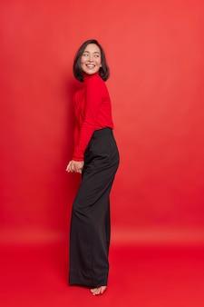 Tiro interior complacida morena tímida mujer asiática mantiene las manos juntas mira hacia atrás sonríe felizmente posa en toda su longitud viste pantalones negros de otoño poloneck aislados sobre una pared roja expresa felicidad