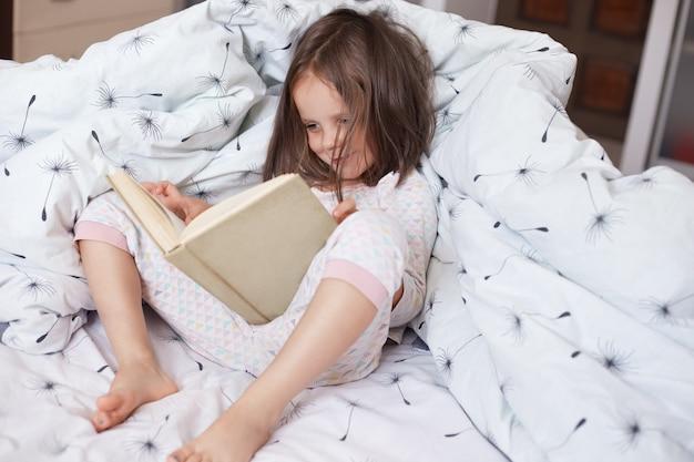 Tiro interior del libro de lectura infantil en la cama debajo de la manta con diente de león. niña pasar tiempo en un dormitorio acogedor. niña haciendo los deberes antes de dormir, leyendo cuentos de hadas. concepto de infancia.