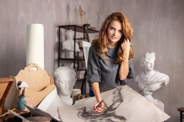 Tiro interior de la pintura femenina profesional del artista en lona en estudio.