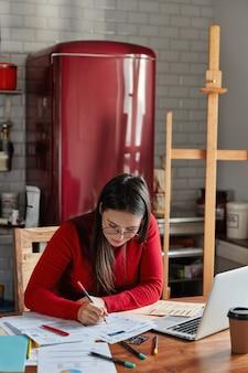 Tiro interior vertical de mujer hace informe financiero, posa en la acogedora cocina con nevera en segundo plano.